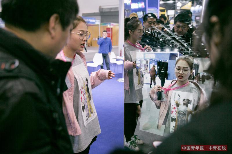 """12月8日,北京国家会议中心,一位来自深圳的展商向观众介绍""""魔镜"""",这款产品结合了AR技术,有模拟化妆、电子动画等功能。本次博览会上的展品云集了云计算、物联网、3D打印、人工智能、虚拟现实、生物科技、石墨烯等科技,无人机、无人超市、无人仓库、智能运动、智慧农业、智能养老、创新旅游等双创产品和业态。段经琨/摄"""