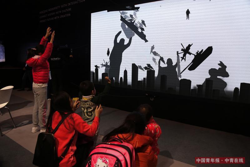 12月9日,孩子和家长体验军事题材的交互设备。中国青年报·中青在线记者 赵迪/摄