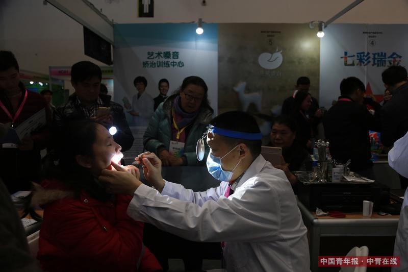 12月9日,一名参展工作人员为参观者检查和矫正嗓音。中国青年报·中青在线记者 赵迪/摄