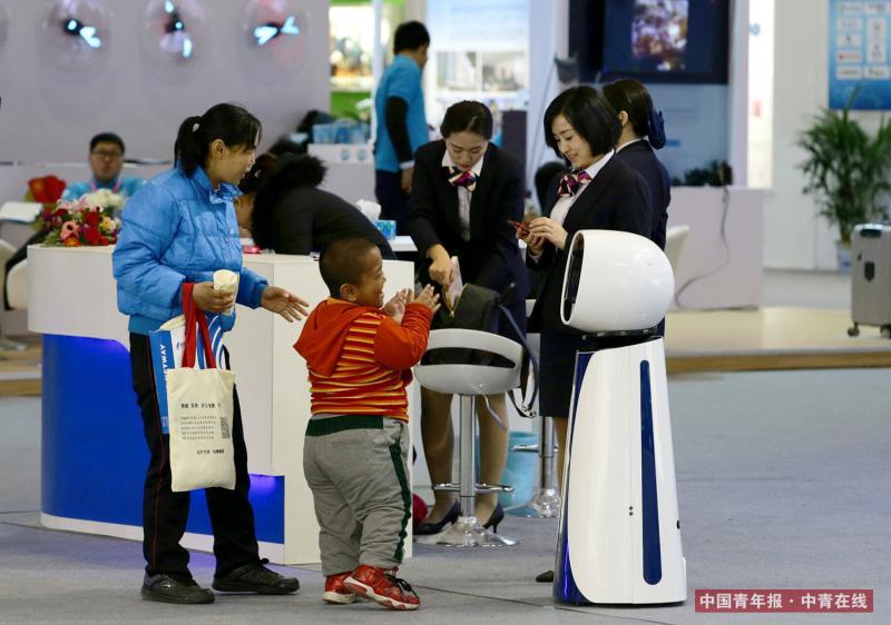 12月9日,江苏银行展台,参观者被一个服务机器人吸引。中国青年报·中青在线记者 陈剑/摄