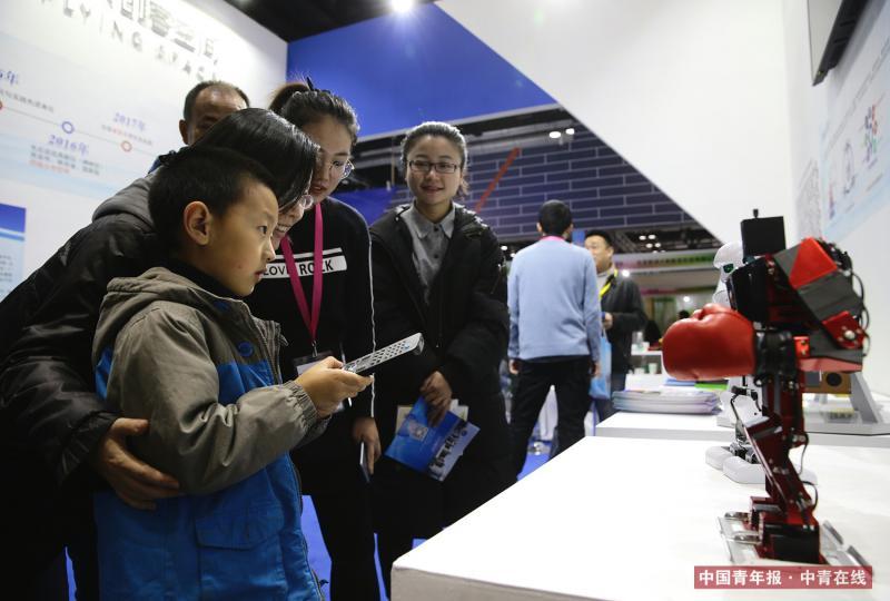 12月9日,西北工业大学飞天创客空间展台,一位母亲带着孩子操作小机器人。中国青年报·中青在线记者 陈剑/摄