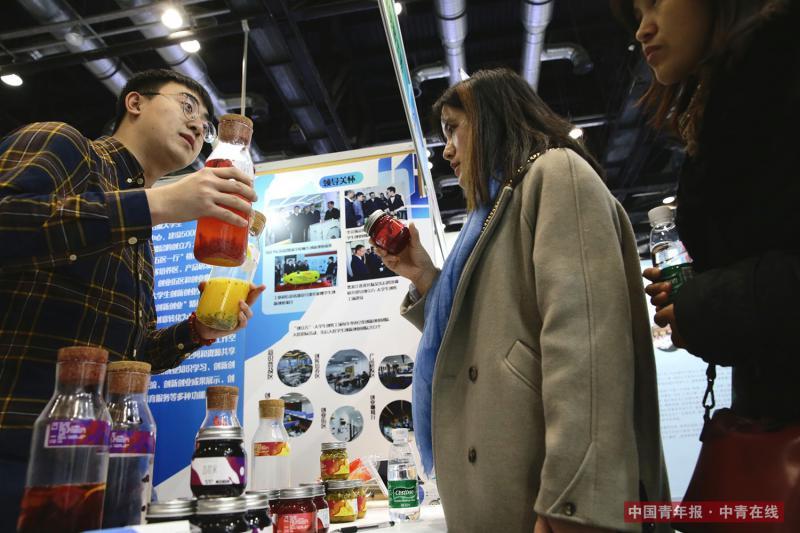 12月9日,哈尔滨工程大学的学生刘剑向两名女青年推荐由他所在的学生创业团队研发生产的鲜果茶。中国青年报·中青在线记者 陈剑/摄