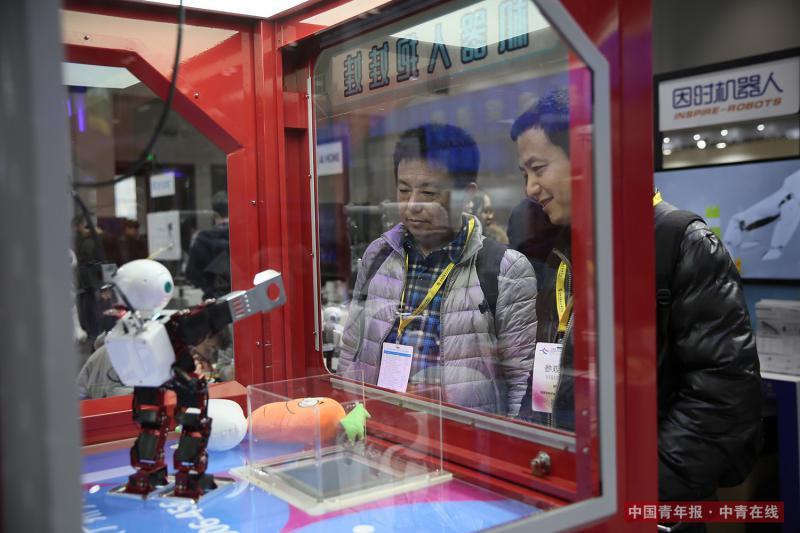 """12月8日,两位参观者观看""""机器人抱娃娃""""的表演。通过程序输入,该款机器人可以按照人的指令将玩具娃娃投入出口。段经琨/摄"""