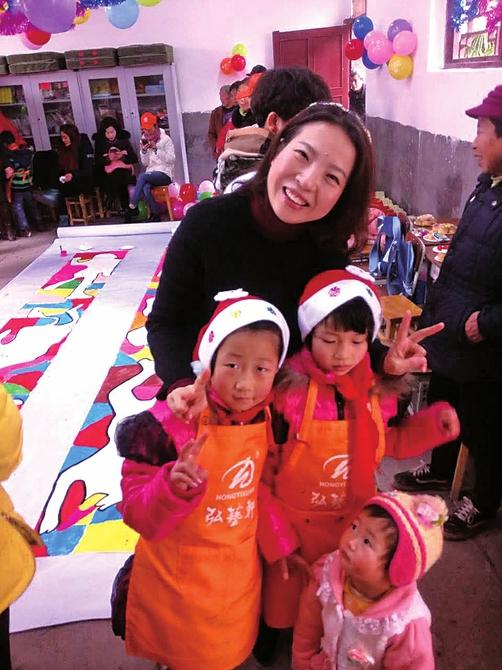 唐红梅与小微企业负责人一道赴龙门村小陪留守儿童过新年。