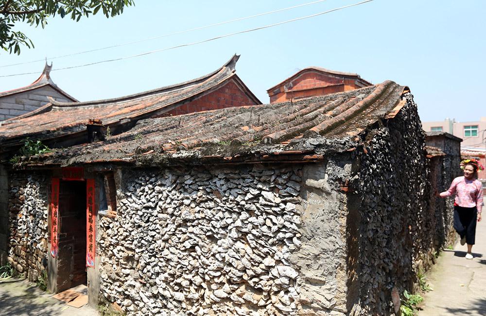 4月24日,在福建省泉州市丰泽区蟳埔村,一名游客参观一处蚝壳厝。