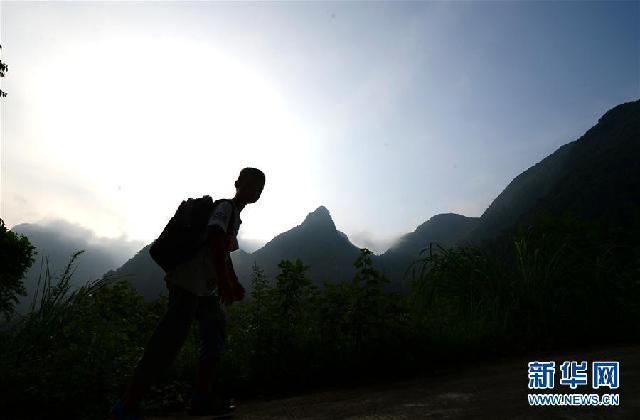 9月4日,在广西柳州市柳城县古砦仫佬族乡大岩垌村,李建文走在上学的
