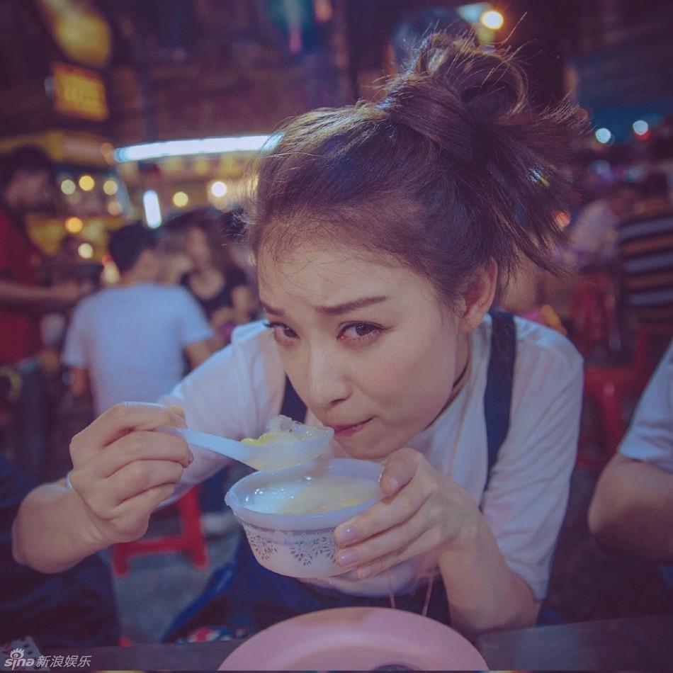 组图:倪妮曼谷街头享美食 丸子头白T恤显青春