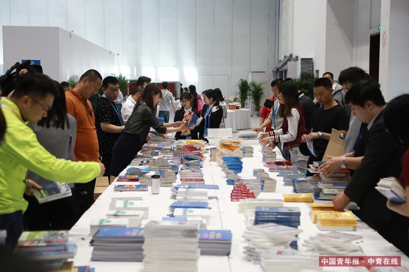 """5月14日,""""一带一路""""国际合作高峰论坛开幕,位于国家会议中心一层的新闻中心的文化展示区受到与会者的欢迎。据报道,新闻中心准备了19种语言的60多种宣传品,供与会者免费取用。中国青年报·中青在线记者 赵迪/摄"""
