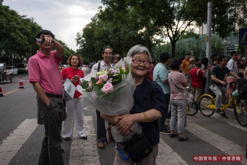 6月8日,北京东直门中学高考考点外,一位年过八旬的老人捧花迎接结束高考的外孙女。下午17时,随着外语科目考试结束铃声的响起,2017年北京地区高考结束。中国青年报·中青在线记者 王婷舒/摄
