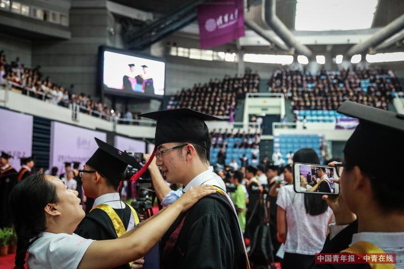 7月2日上午,北京,清华大学2017年本科生毕业典礼暨学位授予仪式现场,一名老师为学生整理衣装。中国青年报·中青在线记者 赵迪/摄