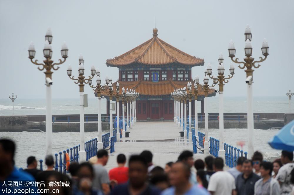 青岛沿海大浪致栈桥封闭 游客排队看海潮