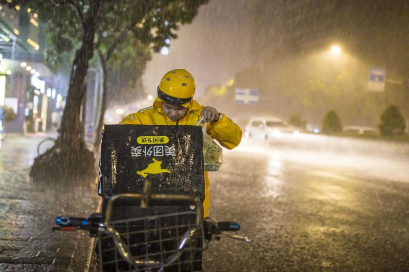 8月22日晚,广州昌岗东路,外卖送餐员在大雨中出行。视觉中国 (编辑:王婷舒)