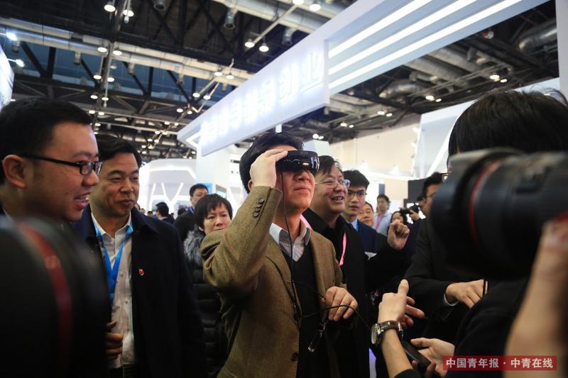 """12月8日,北京国家会议中心,共青团中央书记处常务书记、全国青联主席贺军科现场体验VR眼镜产品。12月8日至10日,2017国际创新创业博览会在北京国家会议中心举行。中国青年诚信建设博览会也同期在这里举行。据介绍,今年的创博会以""""共享与创新""""为主题,展区面积达2.2万平方米,来自中国、德国、法国、瑞典、挪威等10多个国家和地区的440多家机构参展。中国青年报·中青在线记者 赵迪/摄"""