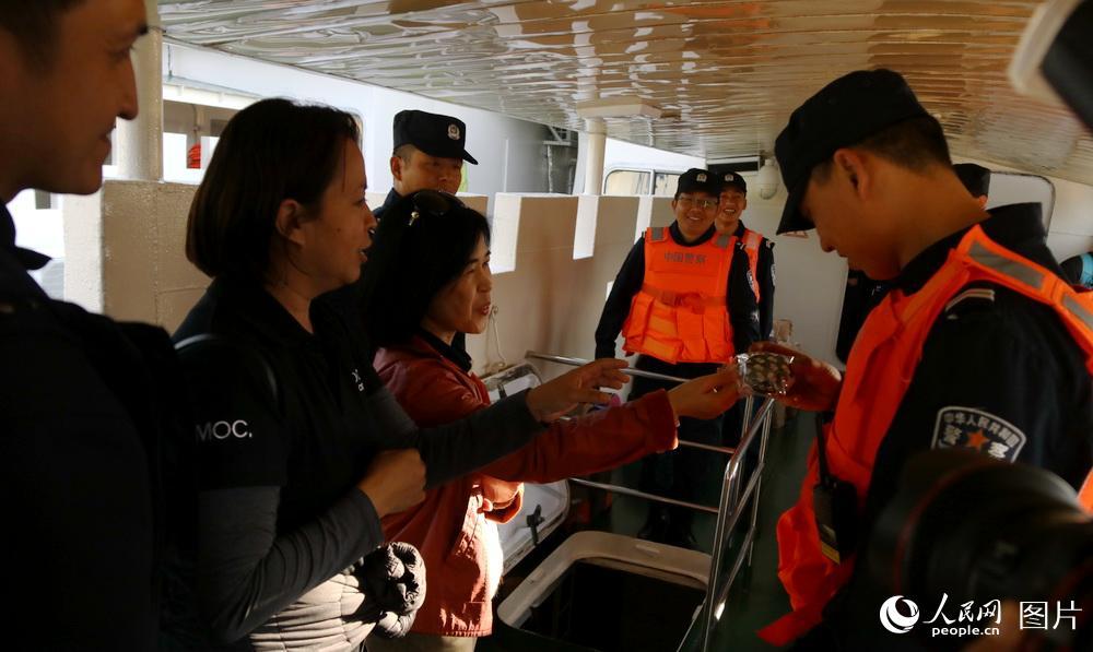 图22 一名泰国女警离开中国巡逻艇时向一名中国边防警察赠送小纪念品。