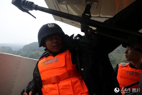 图9 艇首战位值勤的警察赶上阴雨冷风,战友送来御寒的棉衣。