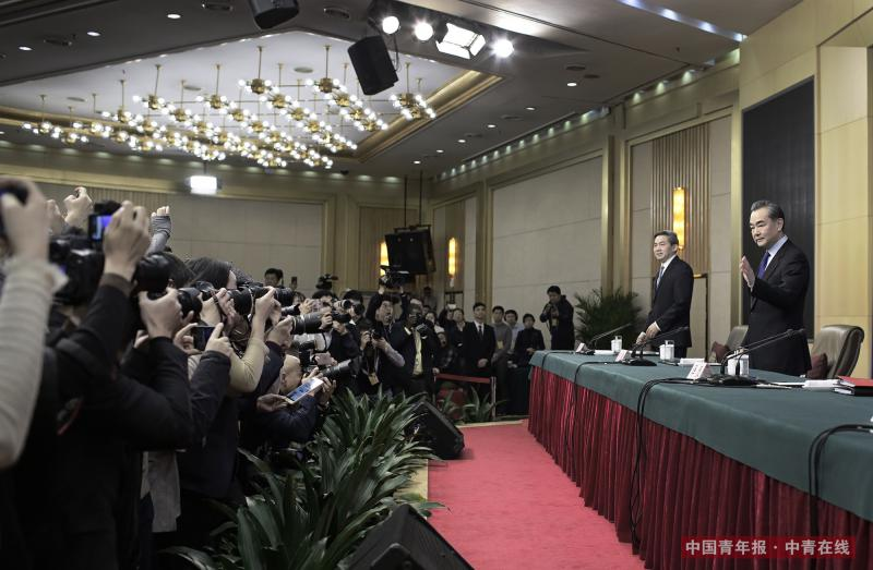 """3月8日上午,在十三届全国人大一次会议的记者会上,外交部长王毅落座前向媒体挥手致意。当天,他就""""中国的外交政策和对外关系""""回答中外记者提问。中国青年报·中青在线记者 赵青/摄"""