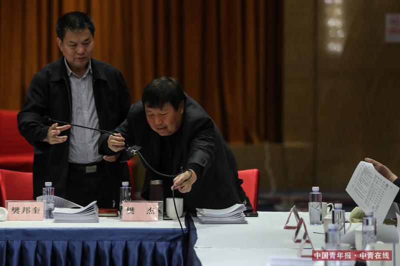 3月12日,北京丰大国际酒店,全国政协十三届一次会议科协界别小组讨论会上,全国政协委员、中国工程院信息与电子工程学部院士樊邦奎(左)拿过话筒准备发言。中国青年报·中青在线记者 赵迪/摄