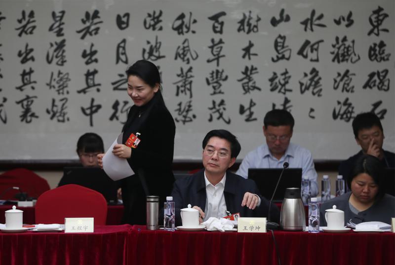 3月9日,北京华北宾馆,全国政协十三届一次会议共青团青联界别小组会议开始前,全国政协委员、西南政法大学经济法学院教授王煜宇(左二)准备落座。中国青年报·中青在线记者 赵迪/摄