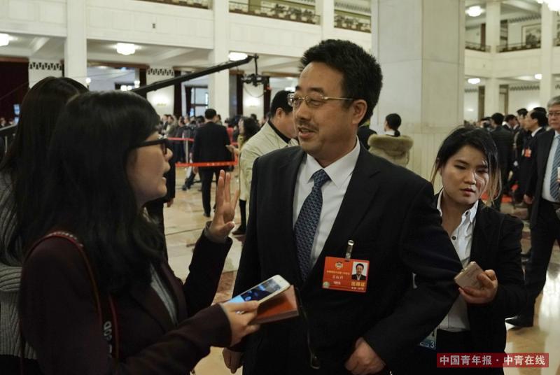 """3月15日,北京人民大会堂,港珠澳大桥管理局总工程师苏权科在""""委员通道""""采访结束后继续回答记者提问。中国青年报·中青在线记者 赵迪/摄"""