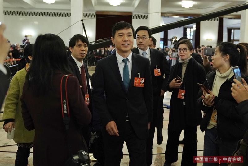 """3月15日,北京人民大会堂,百度公司董事长李彦宏在""""委员通道""""采访结束后被记者包围。李彦宏在采访中预测,再过三五年,完全替代司机的无人驾驶车将会出现。中国青年报·中青在线记者 赵迪/摄"""