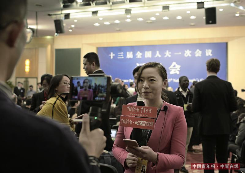 3月8日,十三届全国人大一次会议外交部长记者会开始前,中国青年报·中青在线记者陈婧在会场进行直播。中国青年报·中青在线记者 赵青/摄
