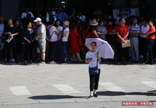 6月7日,北京陈经纶中学高考考点前,一位家长撑着伞在烈日下等候。近日,北京经历高温天气,高考第一天最高气温达 33℃。中国青年报·中青在线记者 陈剑/摄