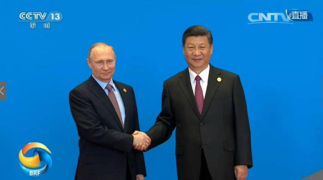 会议开始前,习近平与俄罗斯总统普京握手。