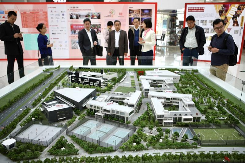 在前海深港青年梦工厂展览馆,工作人员向来访者介绍梦工厂沙盘(12月15日摄)。