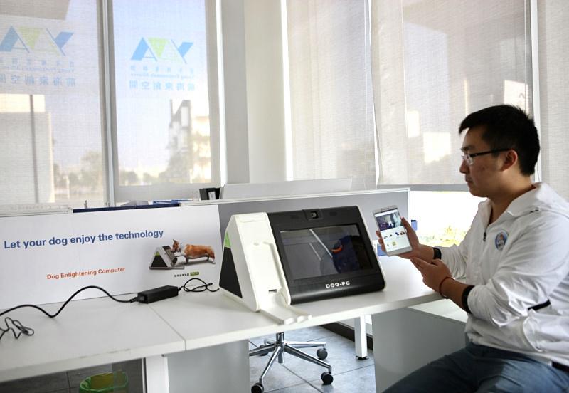 """工作人员在向记者展示宠物狗使用的电脑""""DOG PC""""(12月15日摄)。"""