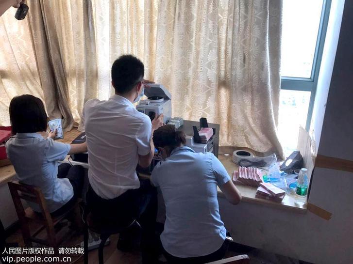 8月15日,办案人员在清点正在查获的钱币。
