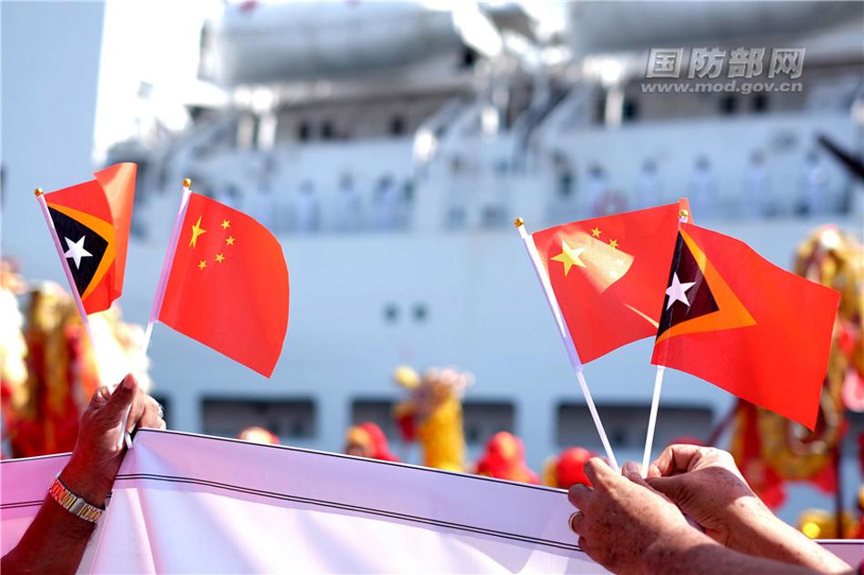 12月14日,在东帝汶帝力港码头,东帝汶民众挥动中国与东帝汶两国国旗欢迎中国海军和平方舟医院船首次到访。江山 摄