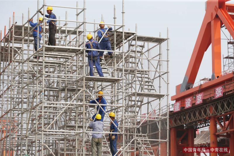 7月20日,中铁大桥局承建的新建京张高铁控制性工程——官厅湖特大桥工地上,工人们搭建高架。据介绍,官厅湖特大桥是世界上第一座适用于设计时速350公里的高寒、大风沙高速铁路的钢桁梁桥。京张高铁全线长约174公里,是助力2022年冬奥会的重点工程,对促进京津冀一体化发展具有重要意义。新建京张高铁计划2019年年底建成通车。中国青年报·中青在线记者 刘占坤/摄