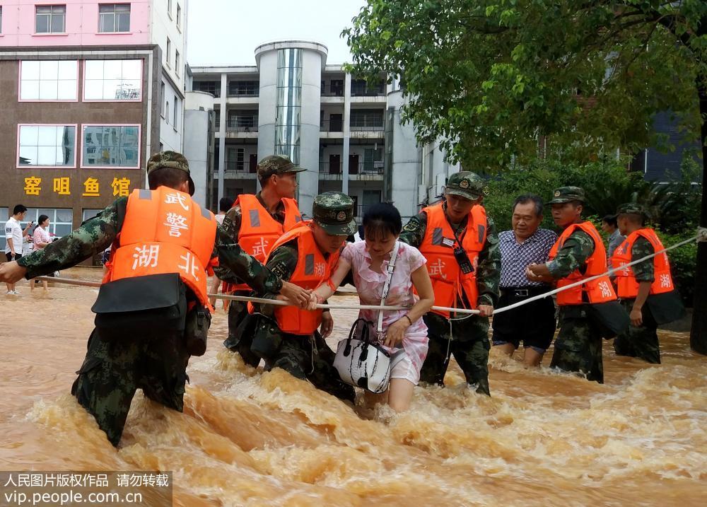 8月13日,武警湖北省总队咸宁支队官兵在咸宁城区转移受灾群众。