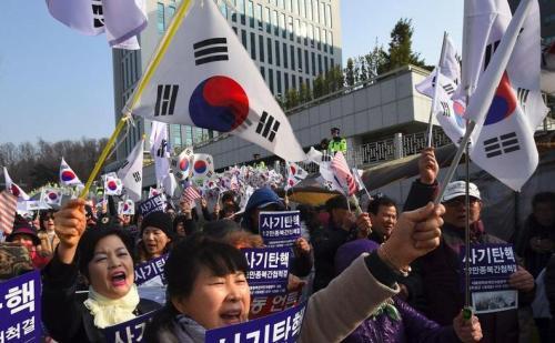 朴槿惠的支持者在她抵达首尔中央地方检察厅时挥舞着国旗,高喊支持她的口号。(图片来源:法新社)