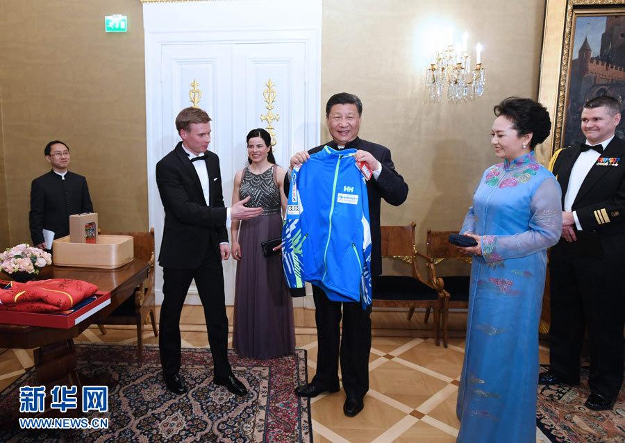 当地时间4月5日晚,国家主席习近平和芬兰总统尼尼斯托在赫尔辛基共同会见刚刚参加完2017年世界花样滑冰锦标赛的中芬两国冰雪运动员代表。习近平夫人彭丽媛和尼尼斯托夫人豪吉欧参加会见。这是芬兰运动员向习近平和夫人彭丽媛赠送运动衣。新华社记者 饶爱民 摄