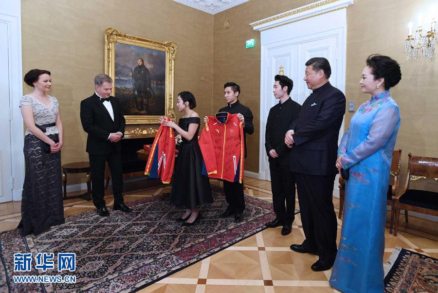 当地时间4月5日晚,国家主席习近平和芬兰总统尼尼斯托在赫尔辛基共同会见刚刚参加完2017年世界花样滑冰锦标赛的中芬两国冰雪运动员代表。习近平夫人彭丽媛和尼尼斯托夫人豪吉欧参加会见。这是中国运动员向尼尼斯托和夫人豪吉欧赠送运动衣。新华社记者 饶爱民 摄