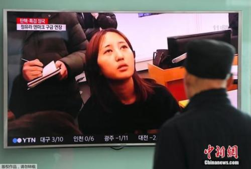 当地时间2017年1月3日,韩国首尔,民众观看顺实之女接受采访的电视报道。