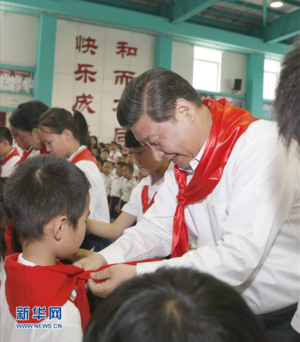 2014年5月30日,在北京市海淀区民族小学的少先队入队仪式上,习近平为新少先队员系上红领巾。新华社记者鞠鹏摄