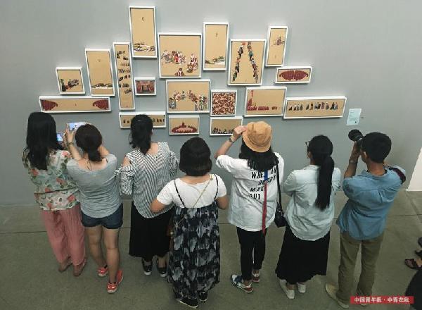 5月27日,北京,中央美术学院美术馆,观众在观看2017中央美术学院研究生毕业作品展,纸本彩墨作品《印象拉卜楞》吸引了不少观众。本次研究生作品展览分为美术馆、7号楼展厅、校园展厅三个部分,共展出中央美院2017届硕、博研究生356名约1200余件毕业作品,作品涵盖中国画、油画、版画、雕塑、壁画、实验艺术、设计、摄影、建筑设计及影像等媒介。展览时间为5月10日至28日。中国青年报·中青在线记者 赵青/摄