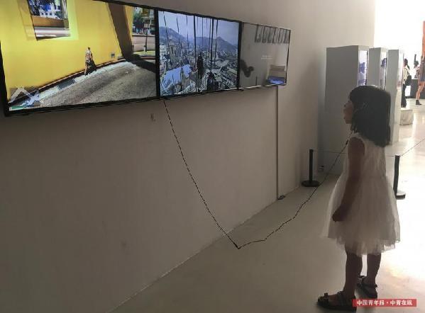 戴着耳机、面对着眼前三块联动的电子屏幕,这个孩子张开了嘴巴。这个作品探讨了游戏中虚拟世界的空间、结构与现实中人情感的关系。中国青年报·中青在线记者 赵青/摄