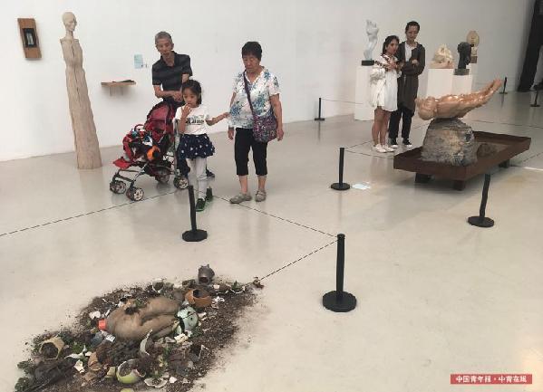 观众走过雕塑作品《无常》。中国青年报·中青在线记者 赵青/摄