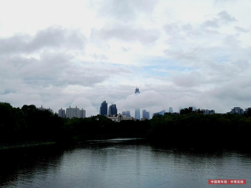 6月23日清晨,北京,一场暴雨如约而至。暴雨后,北京东三环的CBD地区风云变幻,气象万千。一团云雾像白色的丝带将正在建设中的中国尊大楼环绕。中国青年报·中青在线记者 陈剑/摄