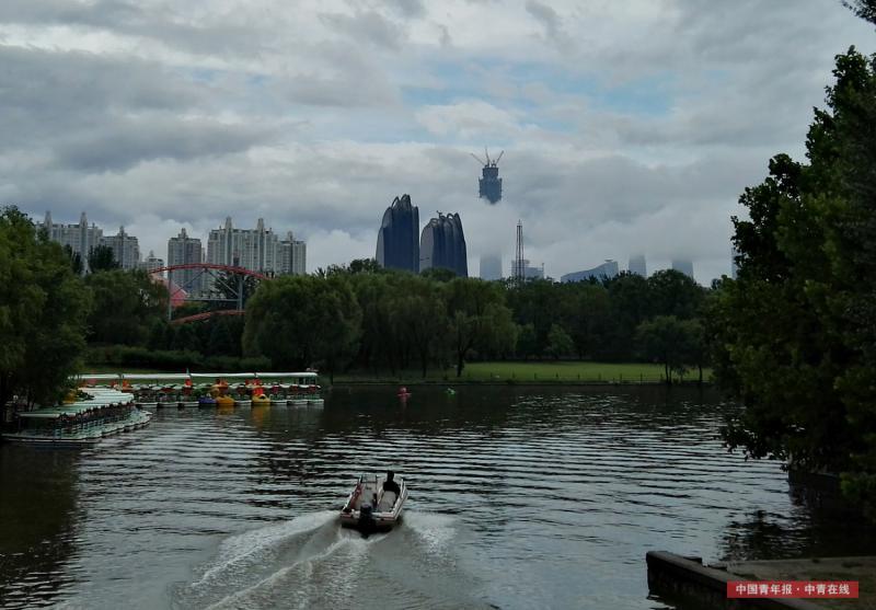 6月23日清晨,北京,一场暴雨如约而至。暴雨后,北京东三环的CBD地区风云变幻,气象万千。一团云雾像白色的丝带将正在建设中的中国尊大楼环绕。中国青年报·中青在线记者 陈剑/摄(编辑:李峥苨)