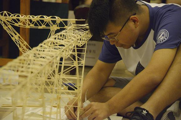 参赛队员认真制作参赛作品 本届结构设计竞赛由陕西省教育厅、陕西省大学生结构设计竞赛委员会主办,西安建筑科技大学承办。赛题为渡槽支承系统的设计与制作,是在我国水资源短缺、时空分布不均匀的条件下,具体解决在地形复杂地区修建输水工程这一实际问题的竞赛比拼。 中国青年报中青在线记者在比赛现场看到:结构制作的过程,需要参赛团队的3名成员紧密配合才能完成。裁、剪、卷、磨、粘,任何环节都容不得丝毫马虎。纤细薄弱的竹条、竹皮在他们手里,变成了一个个精巧的结构件。 经过12小时的制作,7月2日