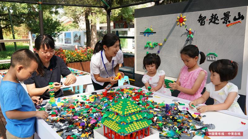 """8月3日,北京景山公园,小朋友参与拼插积木互动体验。景山公园将于8月5日至8月30日首次举办""""智·趣""""嘉年华暑期文化展。展览分为四部分:拼插积木观览区、益智玩具互动区、御园盆景展示区、科普知识介绍区。主展示区共展出由近30万块拼插玩具组成的6大主题展品,20余组拼插积木作品。互动体验区布置了3万块拼插积木池和造型墙,游客可以免费体验互动式组装。中国青年报·中青在线记者 李建泉/摄"""