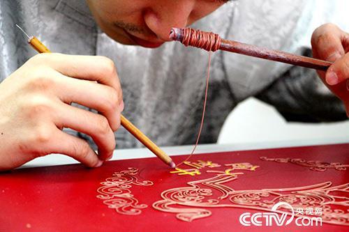 一名工作人员正在制作漆线雕(王甲铸 摄)