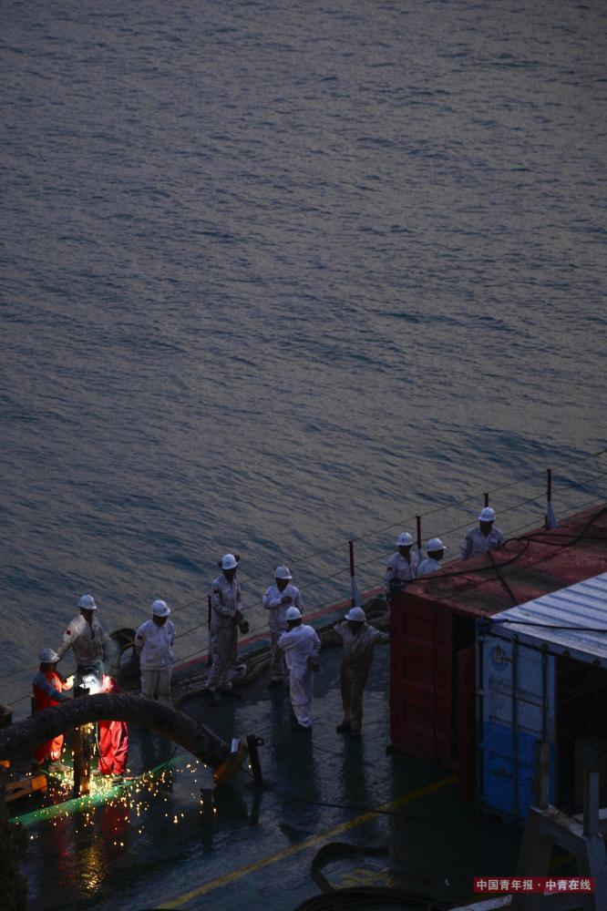 傍晚,船员在甲板上研究打捞方案。