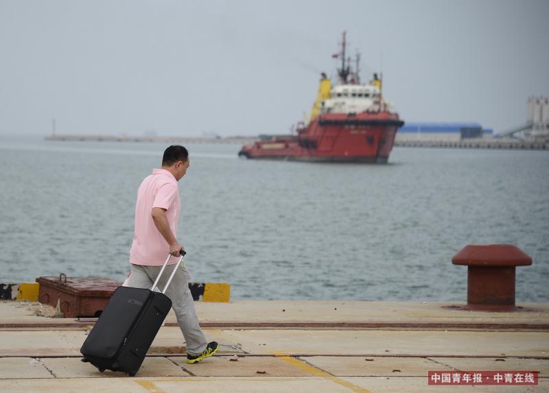 山东东营,楚金勇在码头等待滨海265拖轮靠岸。他要乘坐这条拖轮航行到海上矿区的工程船上进行作业。