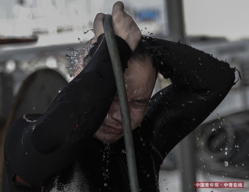 楚金勇在下水前冲凉,既能适应水温,也便于潜水服的穿着。