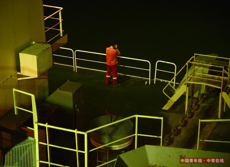 一名船员在甲板上打电话。船员出海时间长,作业地点信号较差,只能偶尔用电话跟家人联系。